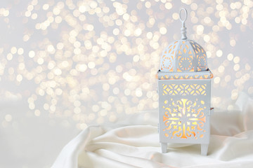 Ornamental white Moroccan, Arabic lantern on silk textile throw. Burning candle, glittering bokeh lights. Greeting card for Muslim community holy month Ramadan Kareem. Festive background.