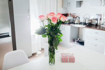 Bouquet of roses with card and gift box left on kitchen. Surprise for woman. Valentine's Day. Modern kitchen design