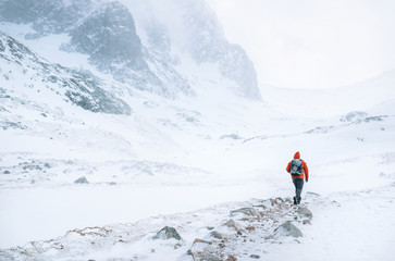 Climber walks alone in high mountains at windy snowy weather