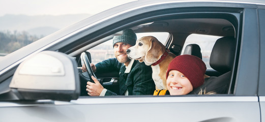Father and son Family traveling by car with beagle dog. They are smiling to camera fixed with safety belts.