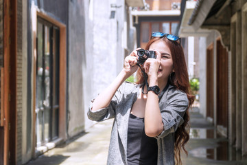 Cheerful photographer young woman with sunglasses holding camera taking photo in city. Traveler young girl use digital camera take photo reflex building while during travel. Photography concept.
