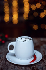 Hot chocolate with marshmallow and chili pepper in a white ceramic cup on Christmas light background.