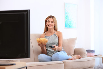 Woman with bowl of potato chips watching TV on sofa in living room