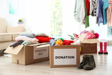 Donation boxes with clothes on floor in living room