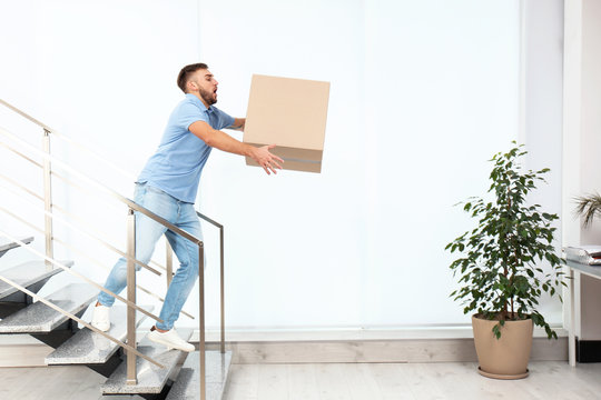 Clumsy young man carrying carton box downstairs indoors. Posture concept