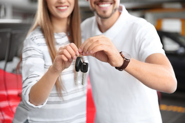 Woman and man with car keys in modern auto dealership, closeup