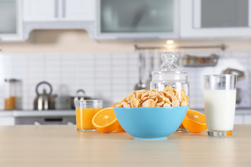 Cornflakes with glasses of juice and milk on kitchen table