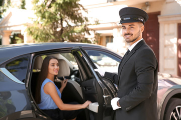 Handsome driver opening car door for young businesswoman. Chauffeur service