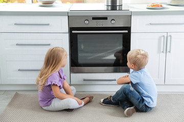 Little kids baking something in oven at home