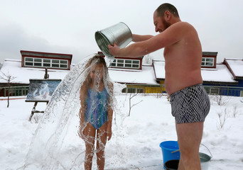 Grigory Broverman, a member of the Cryophile winter swimmers club, pours a bucket of cold water over his 9-year-old daughter Liza during a celebration of Polar Bear Day in Krasnoyarsk