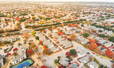 Aerial view Valley Ranch planned unit development with community tennis court in Dallas suburb of Irving, Texas, USA. Colorful fall foliage leaves, row of single-family homes, urban sprawl subdivision