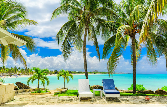 stunning beautiful inviting view on Cuban Varadero beach, tranquil turquoise ocean against blue sky with fluffy clouds and people swimming relaxing in background