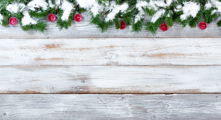 Snowy Christmas evergreen branches and red candles on white vintage wooden planks