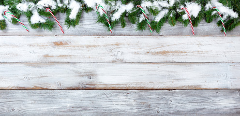 Snowy Christmas evergreen branches and candy canes on white vintage wooden planks