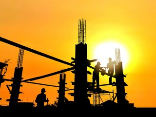 Silhouette construction workers group are pouring concrete on top of building in construction site with blurred sunrise sky background, illustration mode