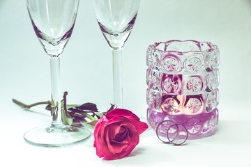 Rose and engage ring near champagne glasses, and candle in Valentine