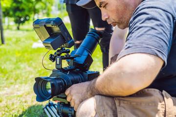 a professional cameraman prepares a camera and a tripod before shooting