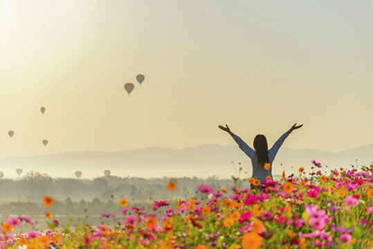 Lifestyle traveler women raise hand feeling good relax and happy freedom and see the fire balloon on the nature tea and cosmos farm in the sunrise morning. Travel and summer Concept