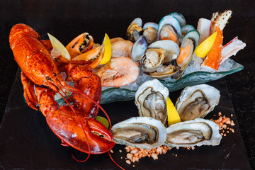 Boiled lobster, fresh oysters, shrimps, mussels and clams served in black stone plate.