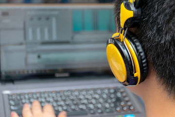video editing,Back view of young man using computer software and wearing headphones.