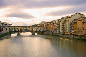 View of the Golden Bridge and the city embankment on a September cloudy morning. Florence, Italy