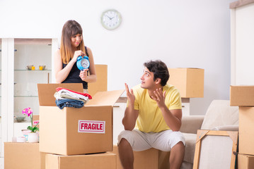 Young couple moving to new flat with fragile things