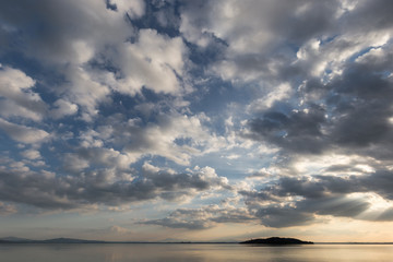 Trasimeno lake (Umbria, Italy) with big clouds at sunset above an island and blue sky