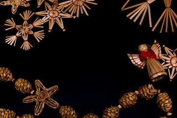 Straw christmas ornaments on black background