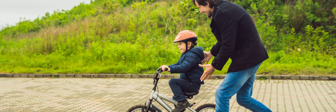 Dad teaches son to ride a bike in the park BANNER, long format