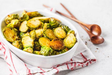 Baked brussels sprouts on a white plate.