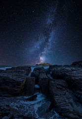 Vibrant Milky Way composite image over landscape of Godrevy lighthouse on Cornwall coastline in England