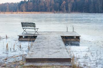 Einsamer Steg am zugefrorenem See im Winter