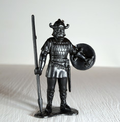 Black viking figurine with spear and shield molded plastic close up Selective Focus
