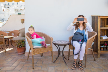 woman taking a photo or video recording with smartphone sitting on chairs and girl making fun