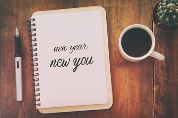 Top view of notebook and text NEW YEAR NEW YOU, cup of coffee over wooden desk.