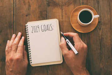 Top view image of 2019 goals list with notebook, cup of coffee over wooden desk.