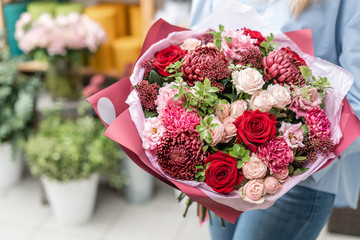 European floral shop. Bouquet of beautiful Mixed flowers in woman hand. Excellent garden flowers in the arrangement , the work of a professional florist.