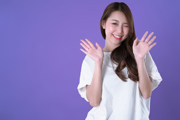 Asian woman glad and hand up, white t-shirt clothing, purple background