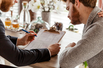 Caucasian respectable couple buying apartment, buyers of real estate ready to conclude a deal with real estate agent after signing documents for realty purchase