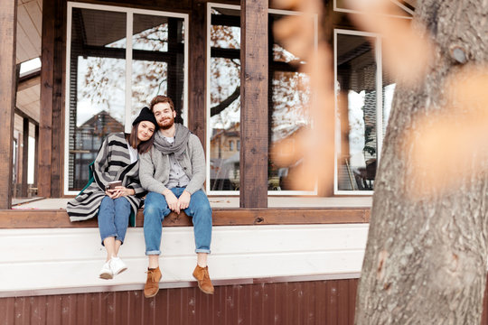 Young couple dressed in stylish warm coats sitting with cups on the terrace of the modern house enjoying beautiful fall view outdoors