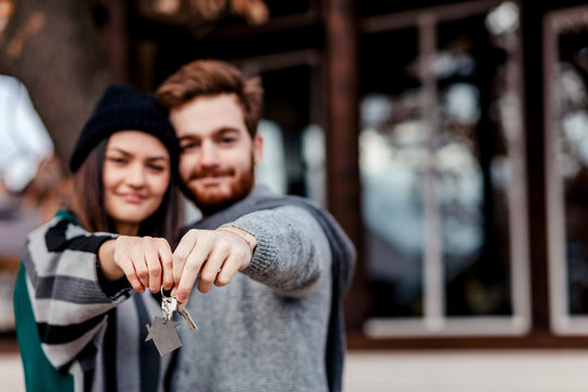 Family, people, real estate purchase concept - smiling couple standing outdoor in house yard, embracing and looking at camera, presenting house key to camera.
