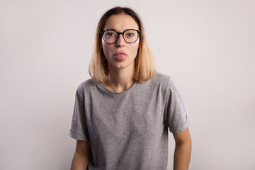 young woman in gray shirt and big eyeglasses show tongue on gray background