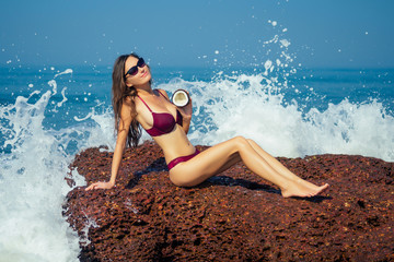 beautiful and young woman in red sexy bikini on the rocks splash of seawater breeze sky and sea background.big waves hitting the rock on which girl posing,tropical paradise beach, wellness and spa