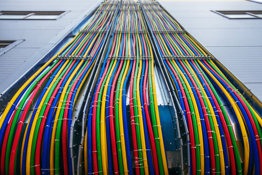Different bright colors electric wires installed on the constructions of industrial building.