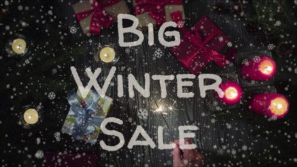Banner Big Winter Sale, white letters, red candles and gifts, falling snow. Top view