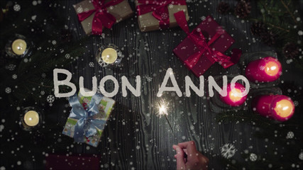 Greeting card Buon Anno, Happy New Year in italian language, falling snow, candles and gifts