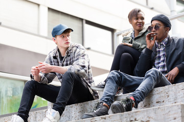 Young boy looking at her friend smoking sitting on staircases