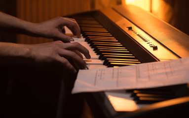 man plays the notes on the piano, close-up, beautiful color background
