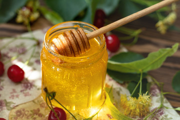 Open glass jar of liquid honey and honey dipper on wooden surface