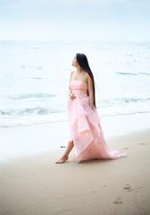 Beautiful young woman walking on Hawaiian beach in pink gown